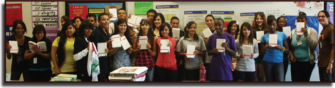 """Zach Serrano and his class display their classroom set of """"A People's History."""""""