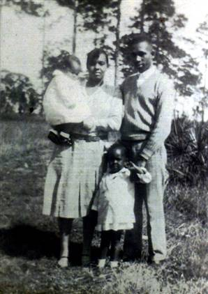 Dec. 25, 1951: Bombing of the Moore Family Home (This Day in History) - The Moore family: Harriette holds daughter Evangeline, Harry, and Annie Rosalea (standing) | Zinn Education Project: Teaching People's History