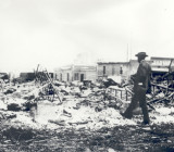 Tulsa Race Riot ruins, an African American man with a camera suveying the rubble.