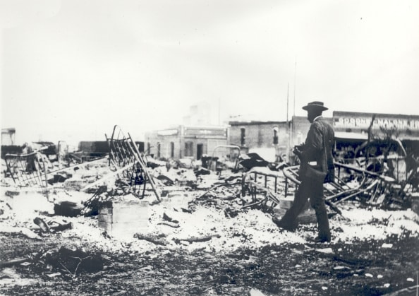 Tulsa Race Riot ruins, an African American man with a camera surveying the rubble.