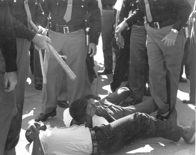 While FBI agents stood by, SNCC volunteers were beaten and arrested by sheriff deputies for attempting to bring water to people (many elderly) waiting in the hot sun for hours to register to vote. © John Kouns.
