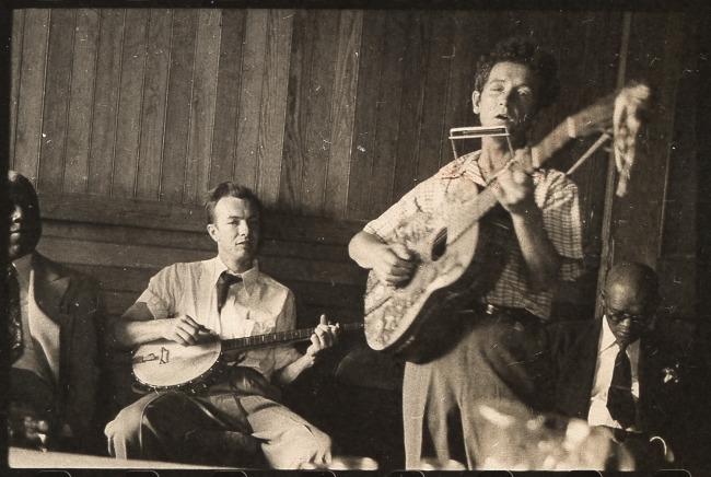 Woody Guthrie plays his guitar. Pete Seeger accompanies on banjo; music journalist Dan Burley sits at left. By Leonard Rosenberg