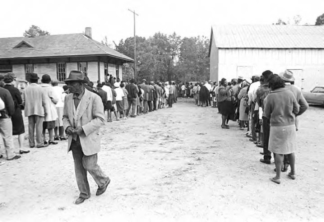 Lines of people standing outside buildings in Lowndes County, Alabama, on election day, Nov. 1966. By Jim Peppler Southern Courier. ADAH.