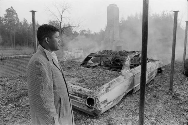 Jan. 10, 1966: Voting Rights Activist Vernon Dahmer is Murdered (This Day in History) -- Harold Dahmer looks over the smoking ruins of his family's home and car | Zinn Education Project: Teaching People's History