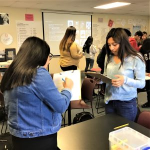 Two students standing in a classroom hold clipboards and converse