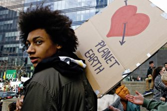 photo of young person at climate justice protest with sign