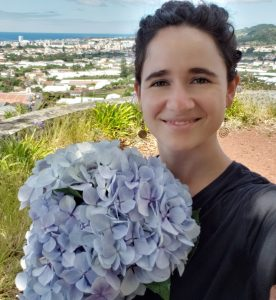Color photo of a woman holding a bouquet of flowers outside