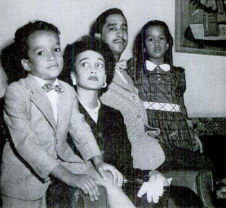Black and white photograph of a family with two adult parents and two children.