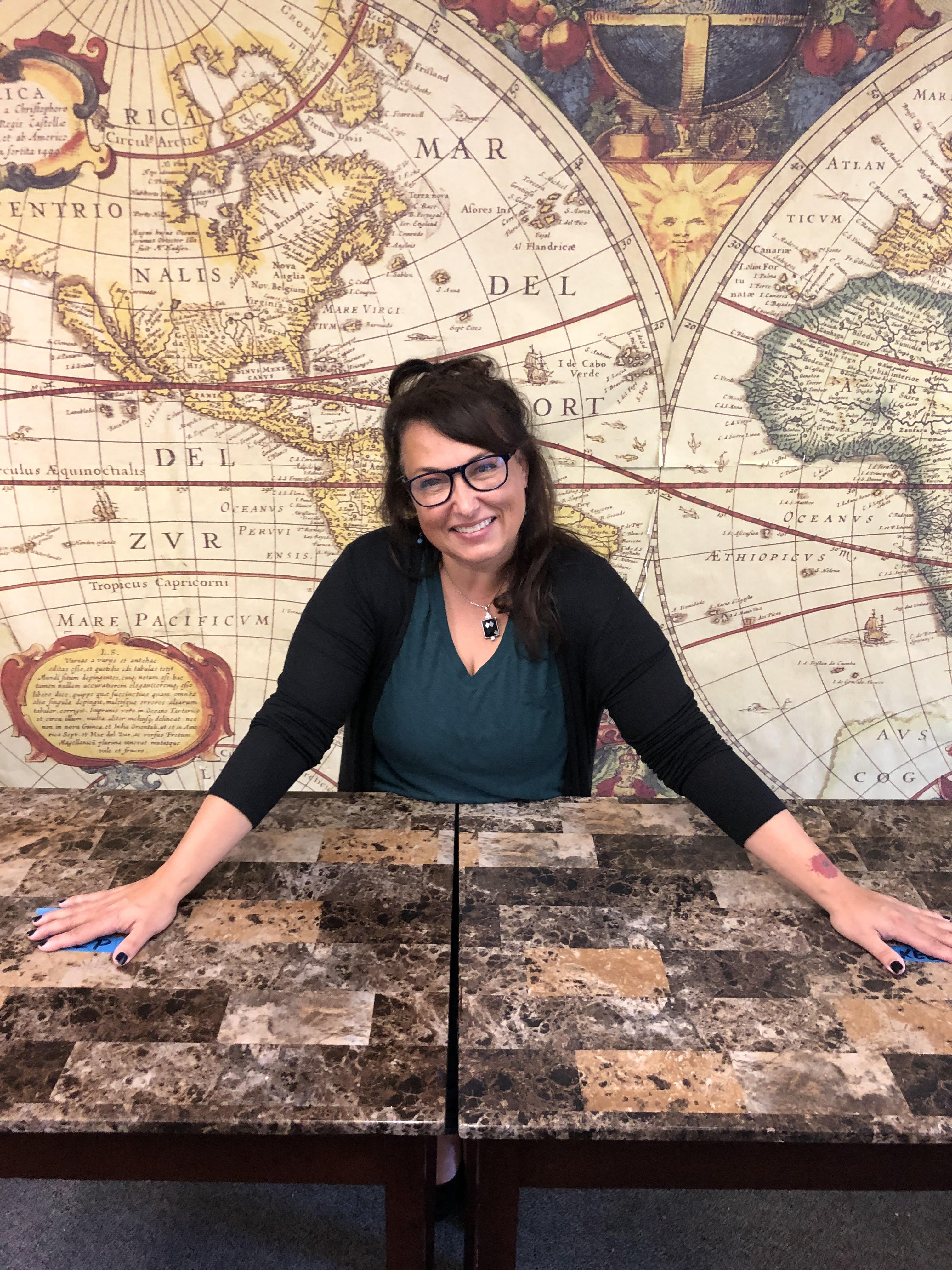 woman smiling, standing in front of a 17th century map of the world