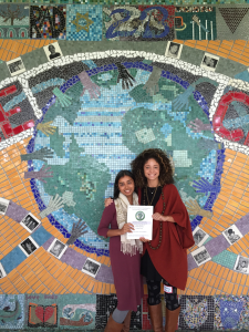 Two women smile and pose in front of a mosaic of the Earth
