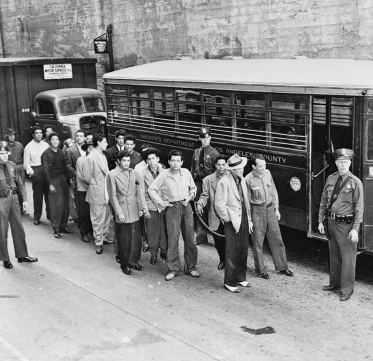 Zoot suiters lined up outside Los Angeles jail en route to court after feud with sailors. Black and white photo.