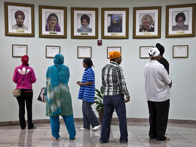 Visitors look at a memorial near the entrance of the Sikh Temple of Wisconsin Wednesday, July 31, 2013, in Oak Creek, Wisconsin