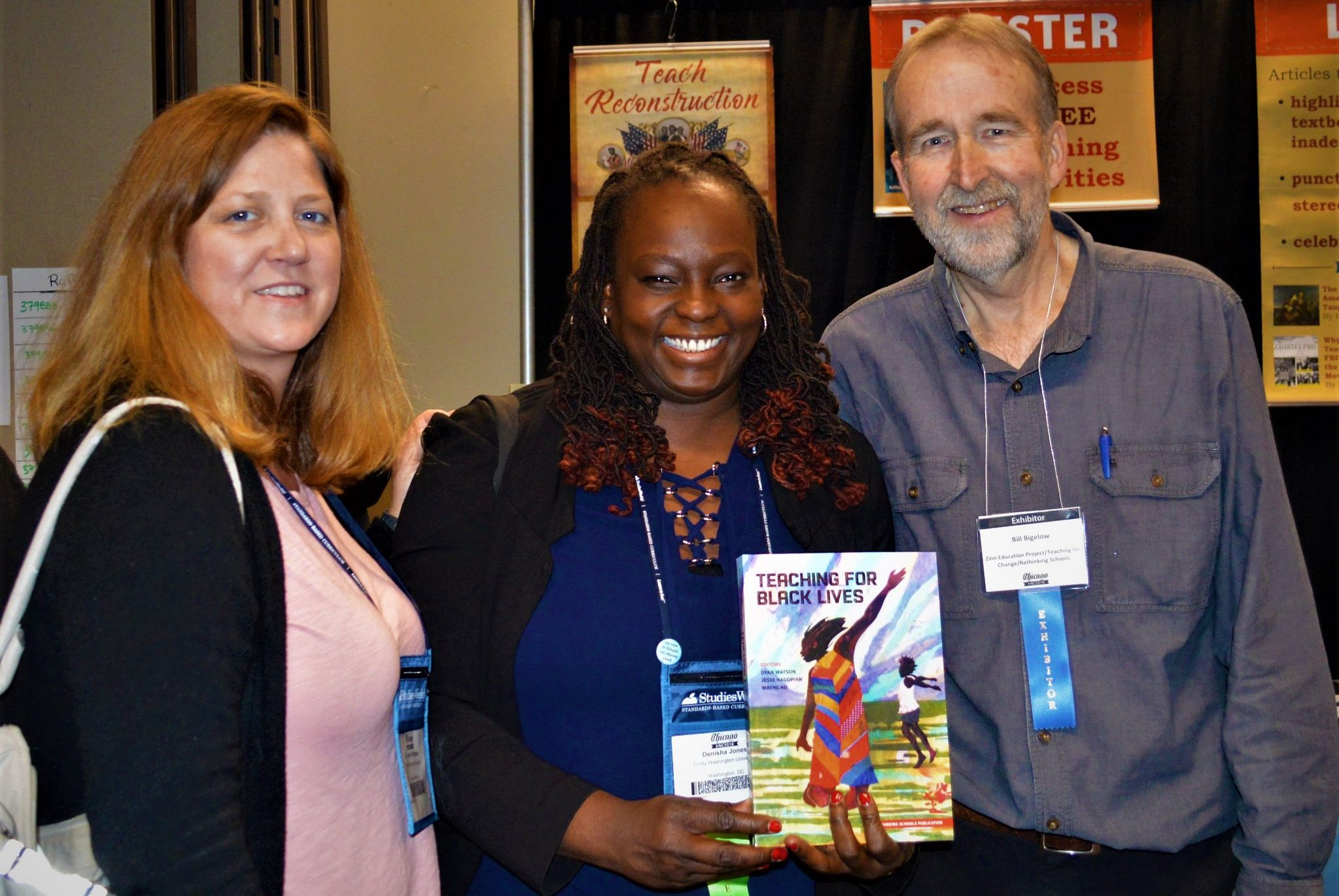 Bill Bigelow and two women at NCSS Chicago 2018 smiling, pose with the book Teaching For Black Lives.