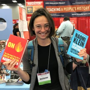 teacher holds up two books about climate justice