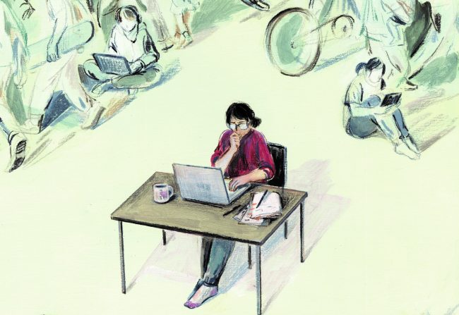 Teacher at desk with computer