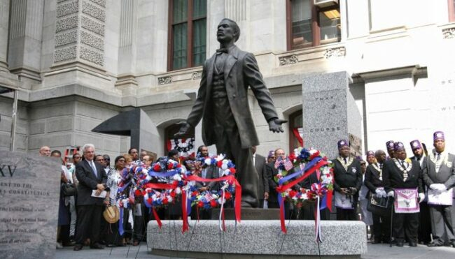 Statue of Octavius Catto with people gathered around it